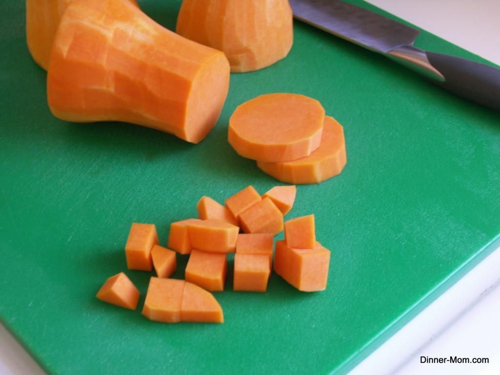 Butternut squash diced on a cutting board.