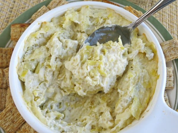 A spoon lifting warm artichoke dip out of bowl