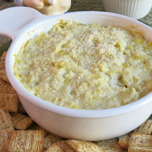 Warm artichoke dip in bowl surrounded by crackers