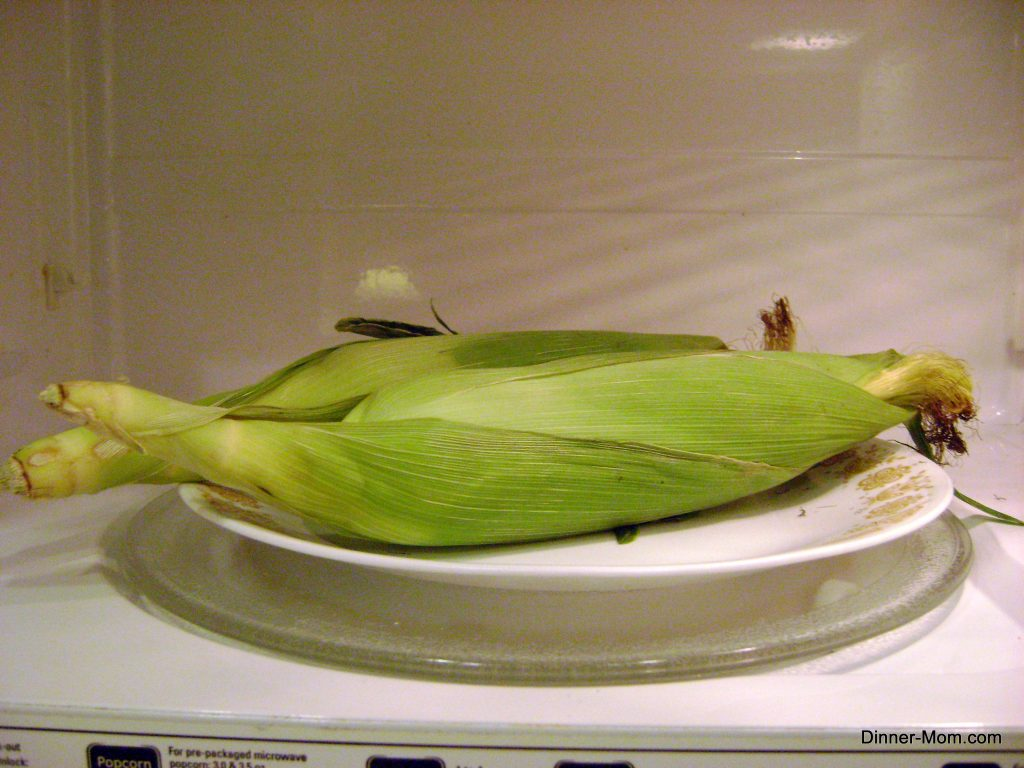 Corn on the cob in husk on plate in microwave