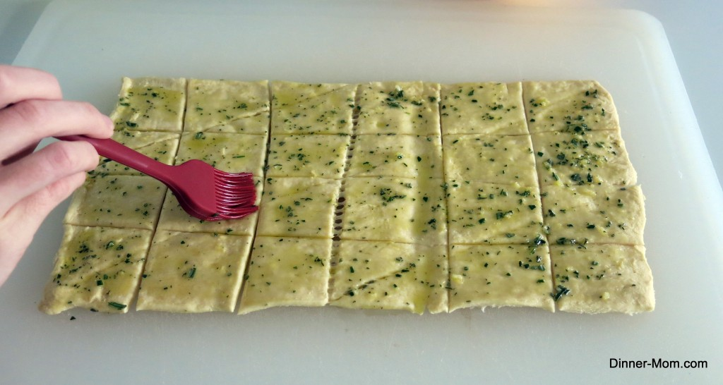 Dough being brushed with olive oil, garlic and rosemary