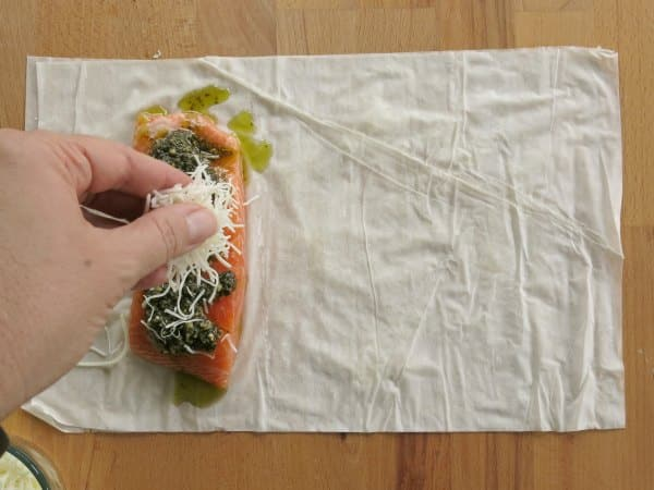 Salmon on top of phyllo dough sheets with pesto and cheese