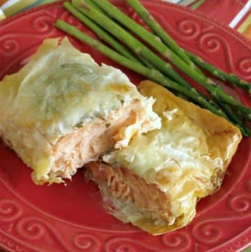 Salmon in phyllo cut in half on a plate with asparagus cut