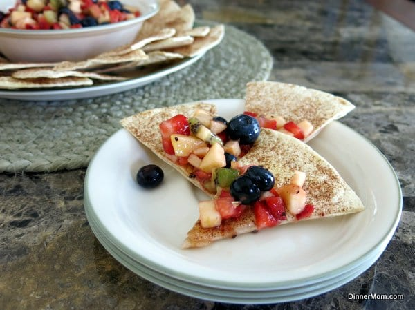 Fruit Salsa on top of cinnamon chips on a stack of plates.