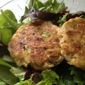 Two crab cakes on salad greens