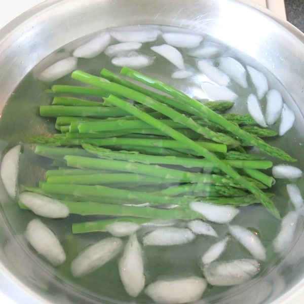 blanched asparagus in bowl with ice