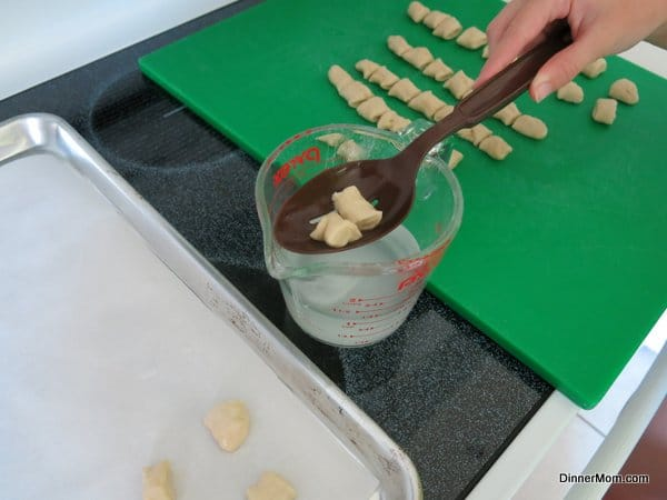 Homemade Pretzel Bites being dipped into baking soda and water mixture with a slotted spoon