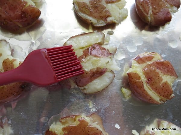 Pastry brush spread oil on potatoes that have been crushed on a baking sheet
