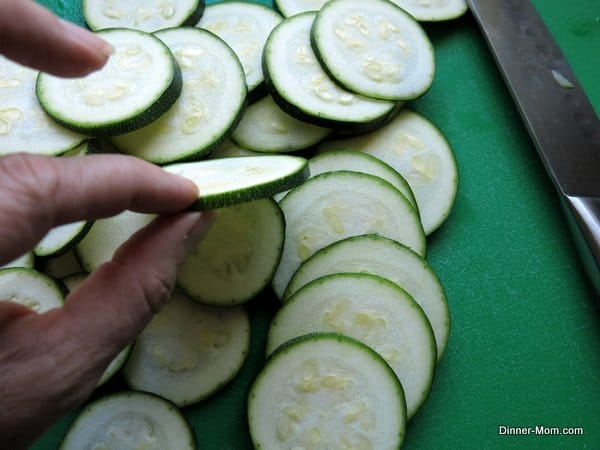 fingers holding Sliced Zucchini with lots of rounds on cutting board
