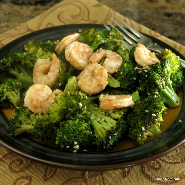Sesame Roasted Broccoli with shrimp on top on a plate