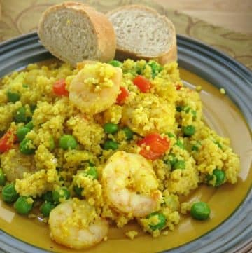 Shrimp Couscous Paella on plate with two pieces of bread