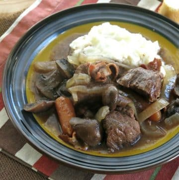 Crock pot beef bourguignon on plate with mashed potatoes