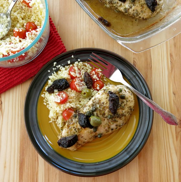 Chicken Marbella with olives and prunes on a plate with couscous