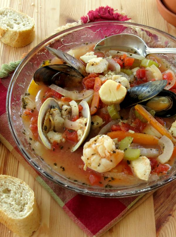 Easy Italian Seafood Stew in bowl with spoon and bread on the side