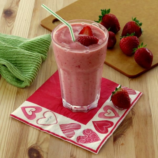 How to Make a Homemade Smoothie + Homemade Smoothie Recipes - Simple Strawberry Smoothie with Yogurt from The Dinner Mom - close up of a strawberry smoothie in a clear glass on a bright pink napkin