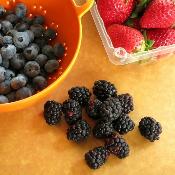 Blueberries, Strawberries and Blackberries on a cutting board