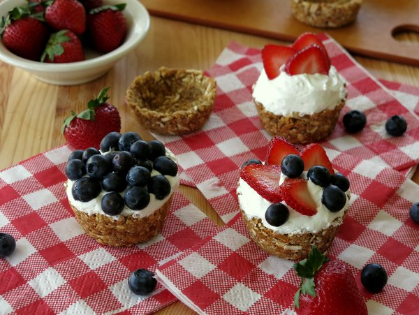 No-Bake Mini Cheesecakes topped with blueberries and strawberries, empty pretzel cups and bowls of berries