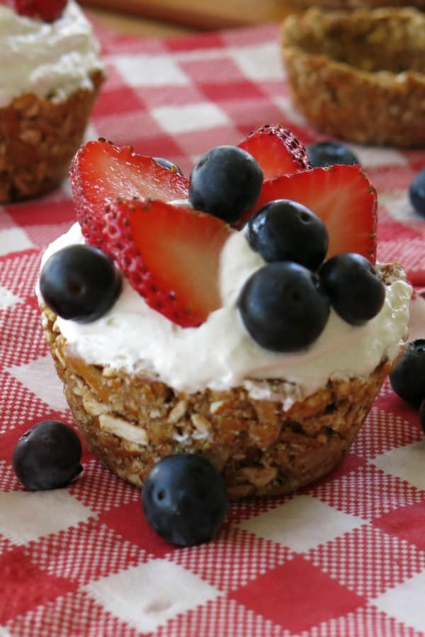 No-Bake Mini Cheesecakes topped with blueberries and strawberries in pretzel crust cup