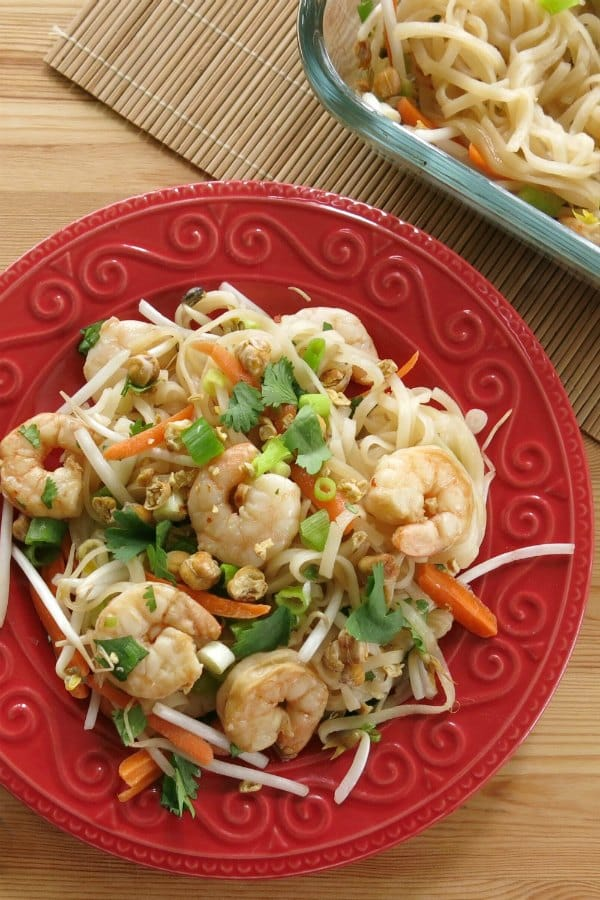 Overhead view of easy shrimp pad thai recipe on plate with baking dish in background