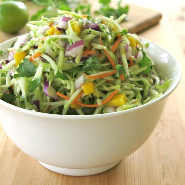 Broccoli slaw with mango and red onion in a bowl