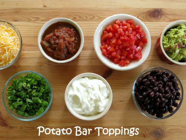 Toppings for baked potatoes in bowls on bar