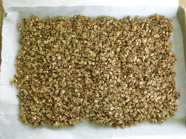 Unbaked granola on a baking sheet lined with parchment paper