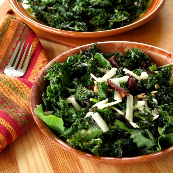 Crispy Kale Chips in a salad bowl with almonds and sundried tomatoes on top