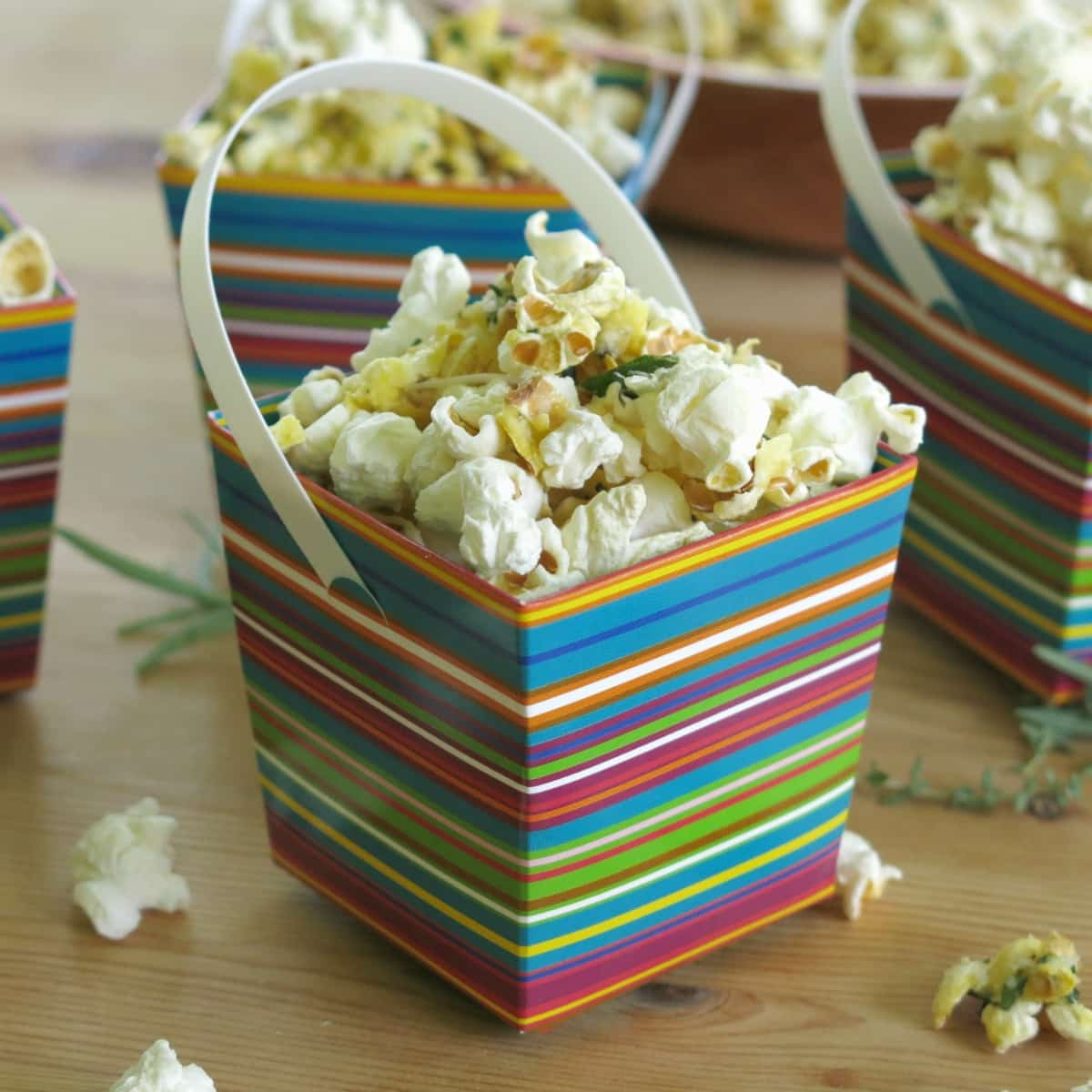 Savory popcorn topped with Parmesan cheese and fresh herbs in serving box.