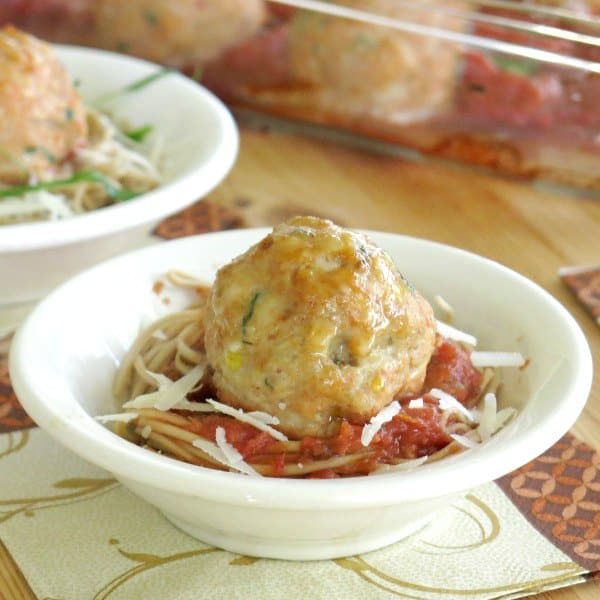 Large Chicken Parmesan Meatball in bowl on top of spaghetti and sauce