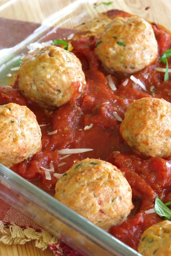 Ground Chicken Parmesan Meatballs on top of sauce in baking dish