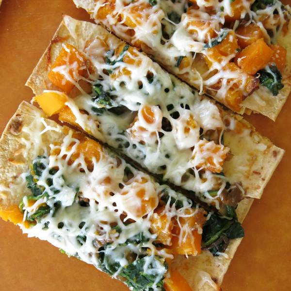 Roasted Butternut Squash Pizza with Caramelized Onion in slices on a board