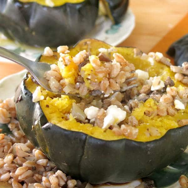 Roasted Stuffed Acorn Squash with Farro and Mushrooms being lifted out with a fork