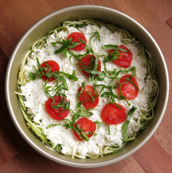 Sliced tomato and basil on uncooked zucchini pizza pie