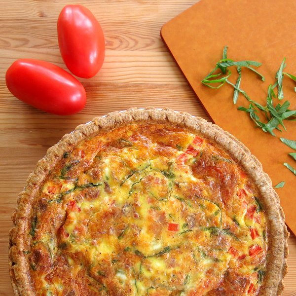 Tomato Bacon Quiche next to plum tomatoes and basil.
