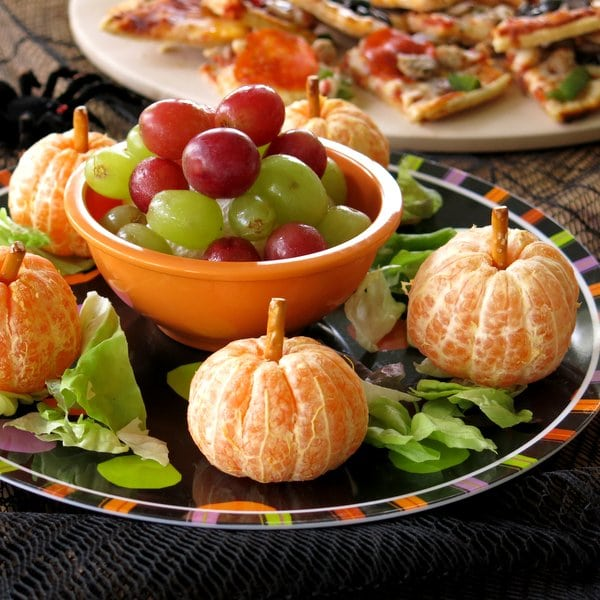 Clementines peeled with a pretzel coming out of the top for Halloween Pizza Party