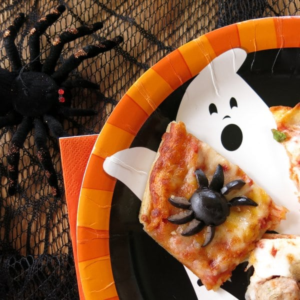 Section of pizza with a spider made out of black olives on a Halloween plate for Halloween pizza party