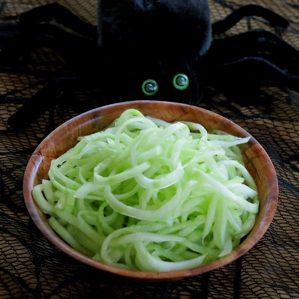 Spiralized Cucumber Salad in a bowl with a spider next to it on a Halloween tablecloth