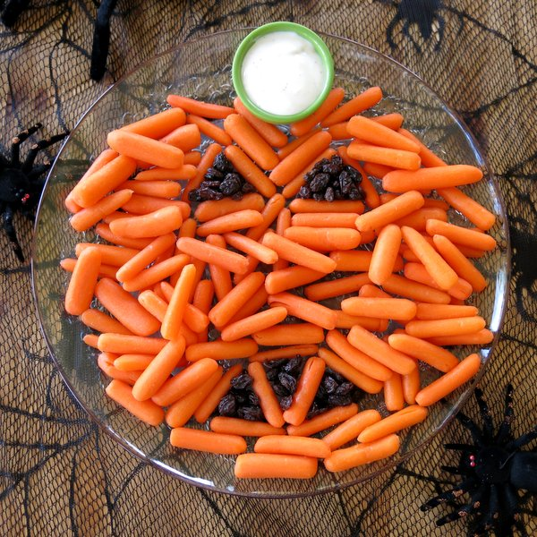Carrots arranged in the shape of a pumpkin with raisins for eyes on Halloween tablecloth