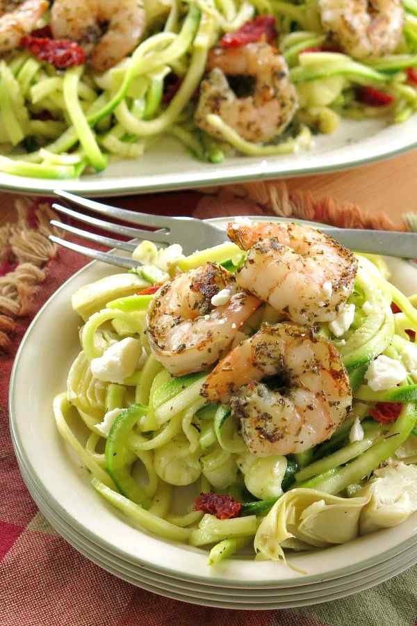 Shrimp Zoodles Recipe on a stack of plates with platter in the background