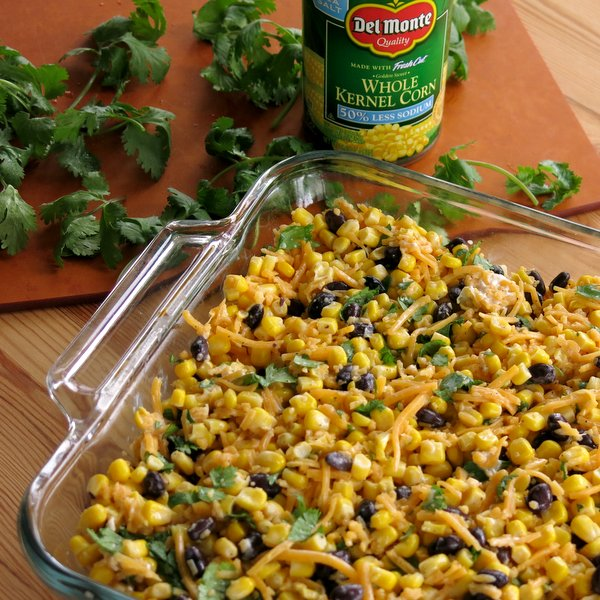 Tex Mex Cheddar Corn Casserole Recipe in baking dish with can or corn in the background