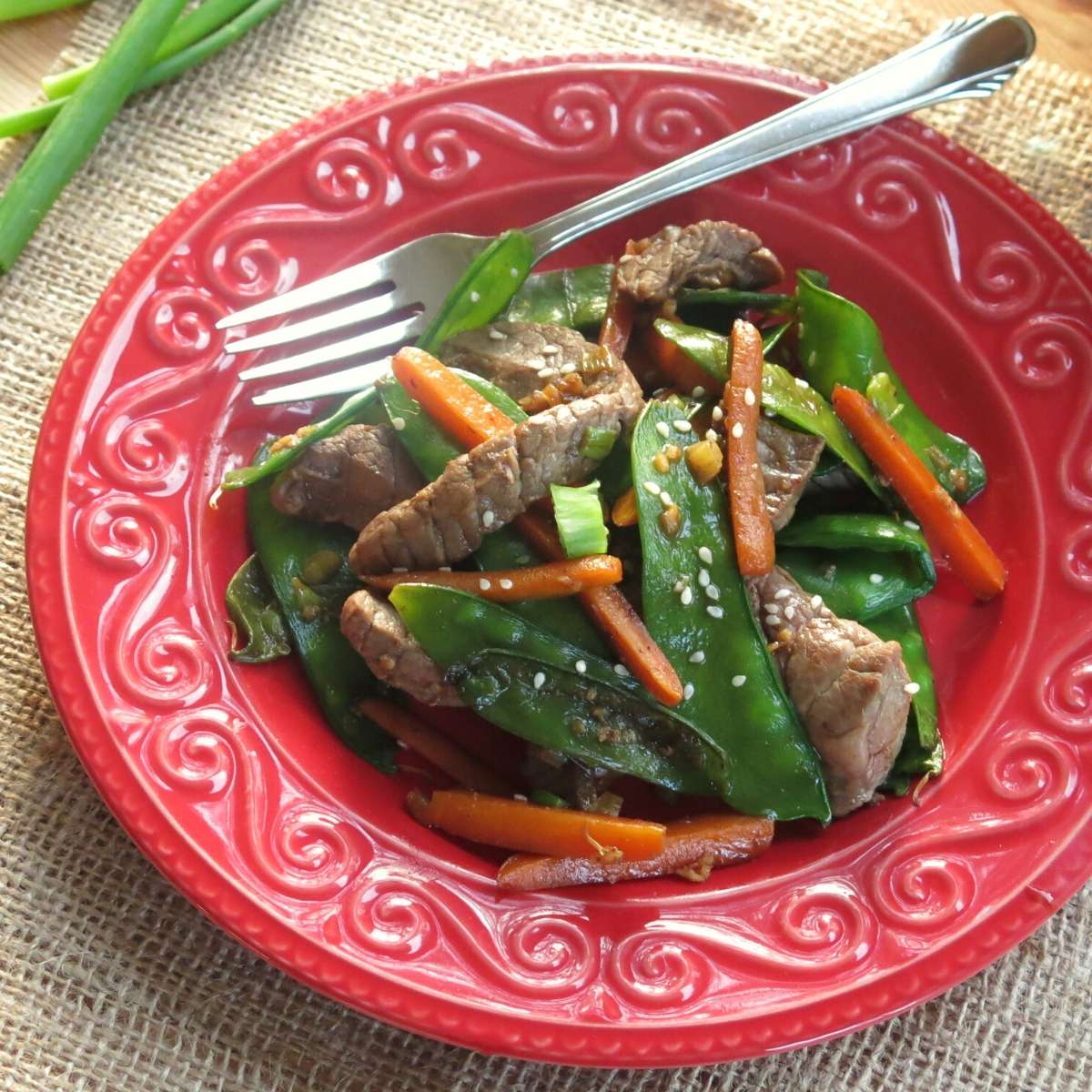 Sesame beef stir fry on plate with fork