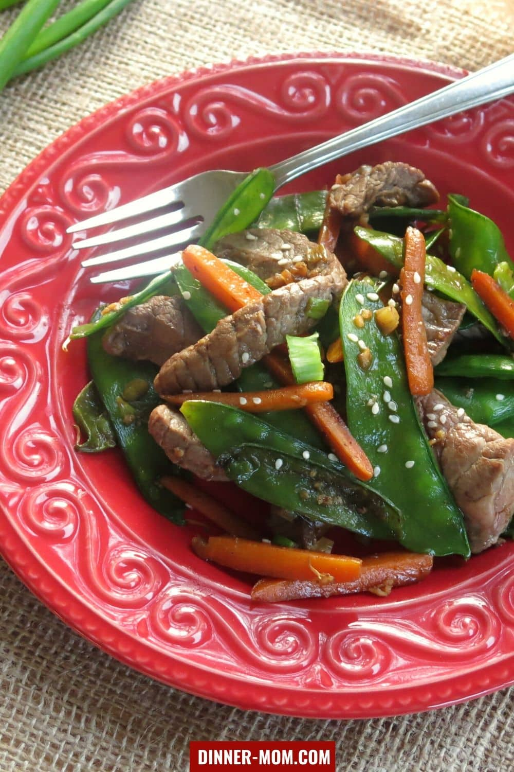 Sesame beef, snow peas and carrots on plate with fork