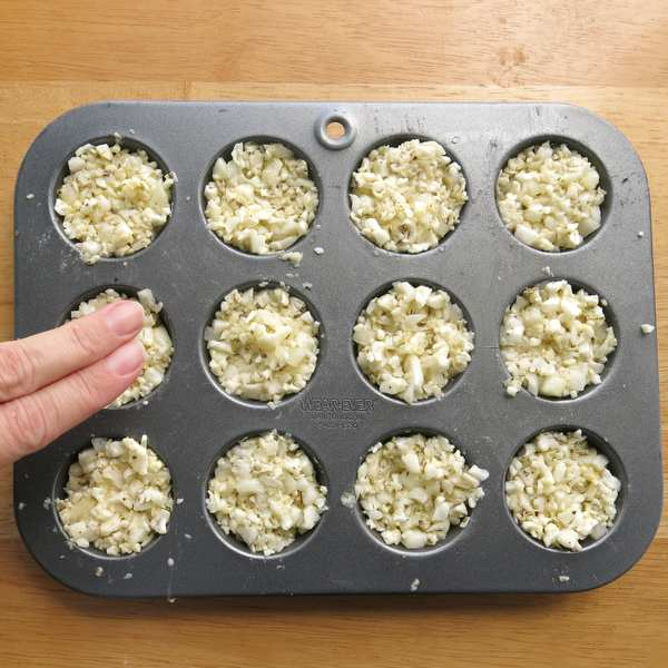Two fingers pressing down on cauliflower egg muffins to compact the mixture
