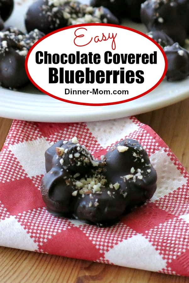 Dark Chocolate Covered Blueberries topped with almonds are so much better than storebought version. It's easy to make these homemade clusters! #chocolatecoveredblueberrries #candyrecipe