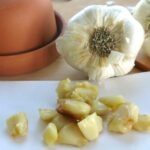 Roasted garlic cloves in a pile in front of bulb of garlic