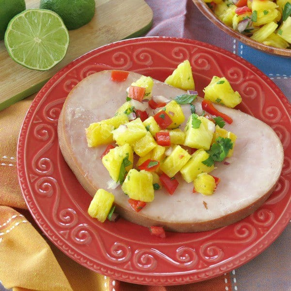 Slice of ham topped with pineapple salsa on a plate.