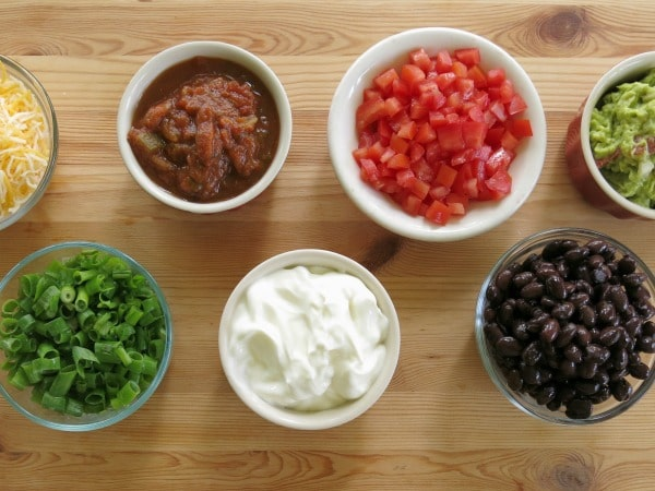 A variety of Mexican toppings in small bowls