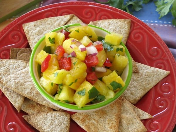 Simple Pineapple Salsa in bowl surrounded by homemade tortilla chips
