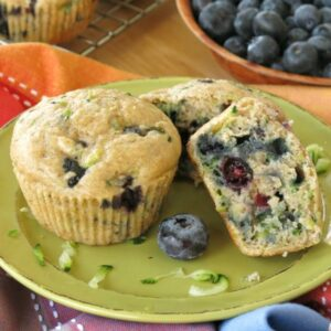2 Zucchini Blueberry Muffins on plate with 1 cut in half