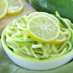 Lemon Garlic Zucchini Noodles in bowl with lemon slices on top
